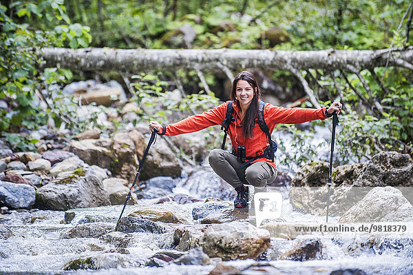 Österreich  Altenmarkt-Zauchensee  junge Wanderin am Fluss hockend