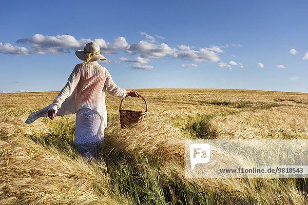 Estland  Frau  die in einem Getreidefeld mit Korb in der Hand läuft