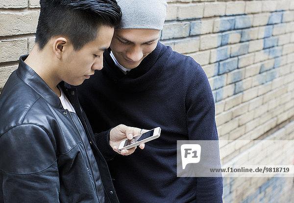 China  Hongkong  junges männliches schwules Paar  das auf der Straße steht und auf das Smartphone schaut.