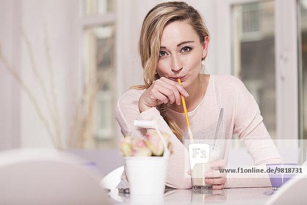 Porträt einer blonden Frau  die in einem Café sitzt und Latte Macchiato trinkt.