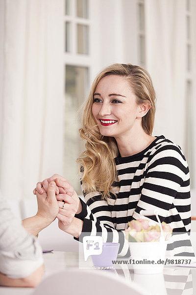 Lächelnde blonde Frau  die in einem Kaffee sitzt und Händchen hält.