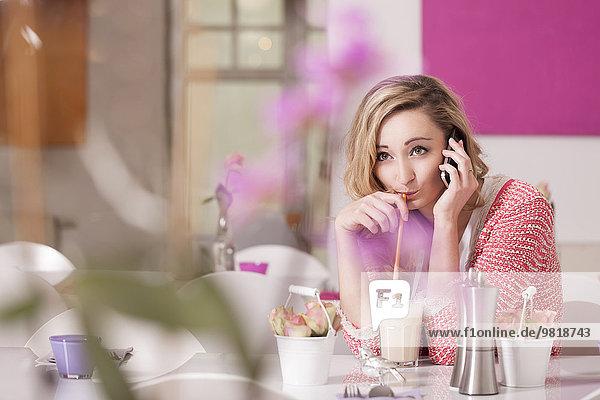Lächelnde blonde Frau sitzt in einem Kaffee mit einem Glas Latte Macchiato beim Telefonieren.