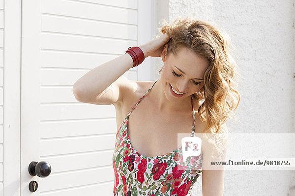 Lächelnde junge Frau mit der Hand im Haar