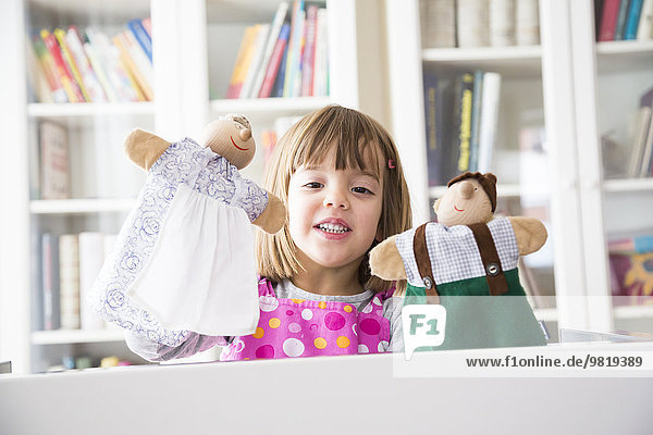 Girl at home playing puppet theater