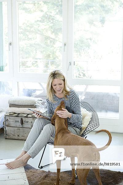 Frau mit Hund und digitalem Tablett zu Hause