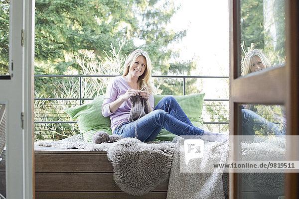 Blonde Frau sitzend auf dem Balkon strickend