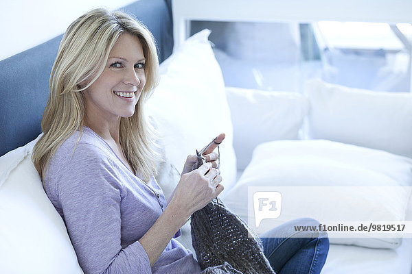 Portrait of smiling blond woman sitting on couch knitting