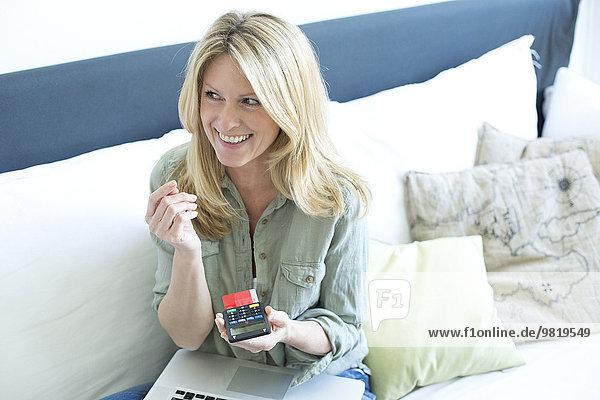 Lächelnde blonde Frau mit Laptop über Online-Banking