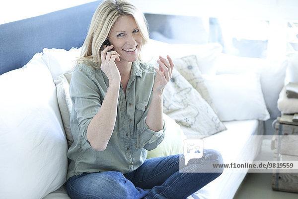 Lächelnde Frau sitzend auf der Couch telefonierend