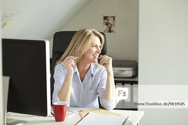Lächelnde Frau sitzt zu Hause am Schreibtisch
