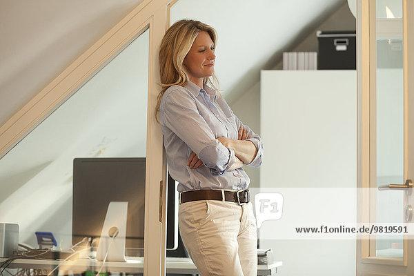 Lächelnde Frau auf dem Dachboden stehend