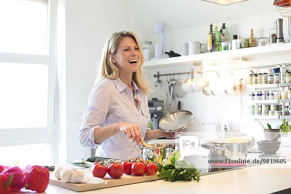 Glückliche Frau beim Kochen in der Küche