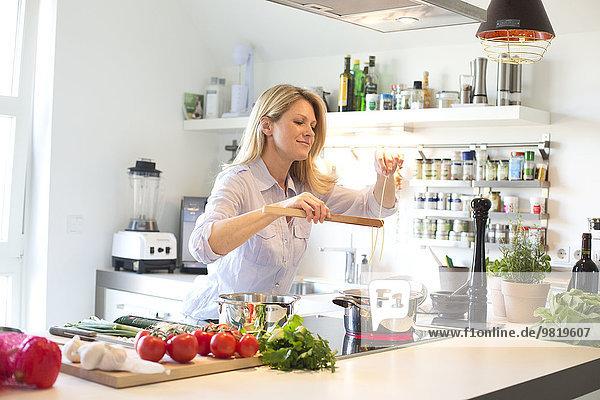 Lächelnde Frau kocht Spaghetti in der Küche