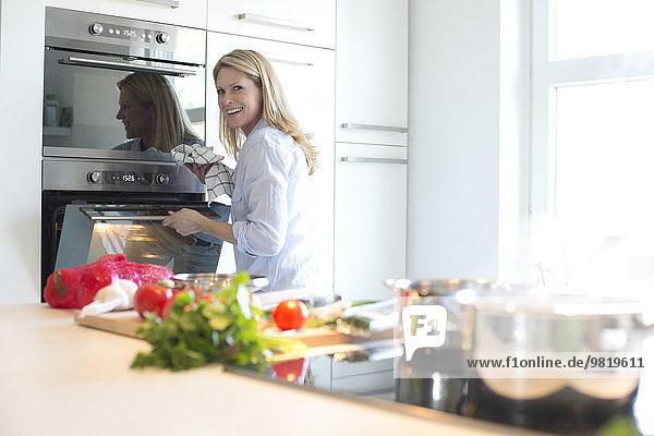 Lächelnde Frau am Ofen in der Küche