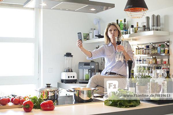 Frau in der Küche mit einem Glas Rotwein bei einem Selfie