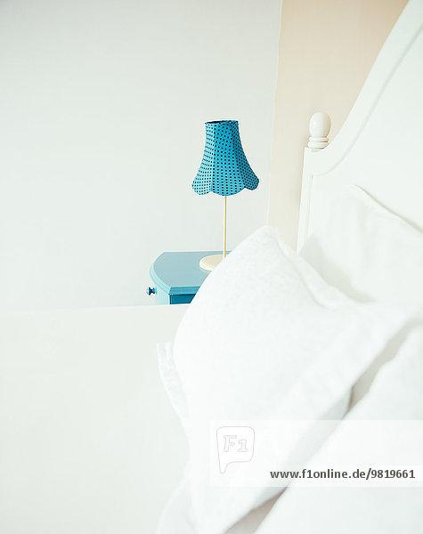 Indonesien  Bali  Tischlampe auf blauem Nachttisch und Bett im Schlafzimmer einer Ferienvilla