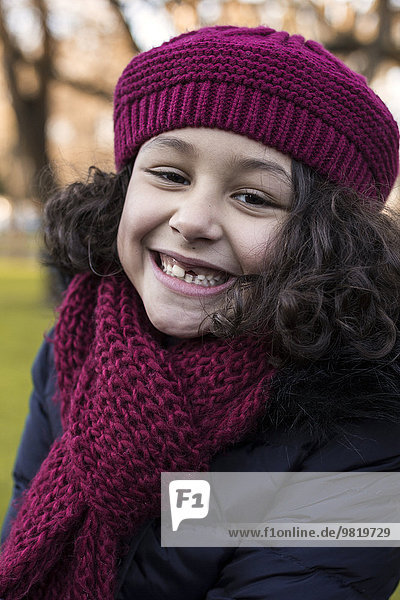 Portrait of smiling little girl with tooth gap wearing wool cap and scarf