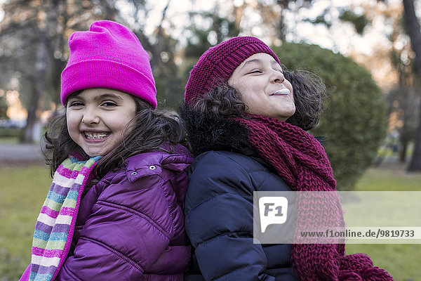 Portrait of two happy little girls back to back in a park on a winter day