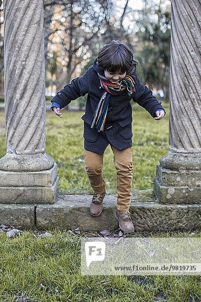 Kleiner Junge  der sich an einem Wintertag im Park amüsiert.