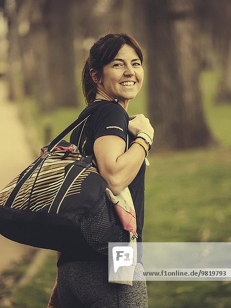 Spanien  Gijon  Frau mit Sporttasche nach dem Training
