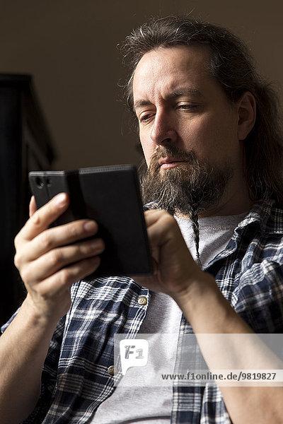 Mann mit geflochtenem Bart auf dem Smartphone