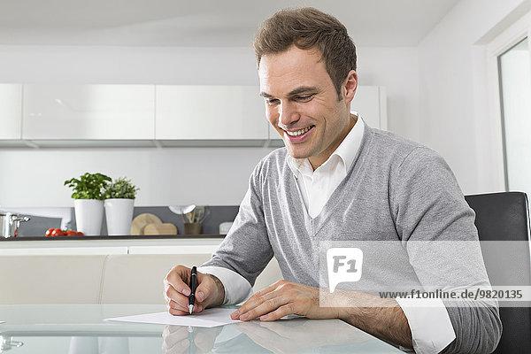 Lächelnder Mann sitzt in der Küche und schreibt etwas auf.