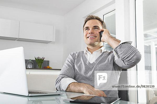 Lächelnder Mann in der Küche mit Laptop und digitalem Tablet-Telefonieren mit Smartphone