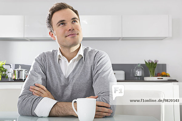Portrait of smiling man sitting in kitchen with cup of coffee