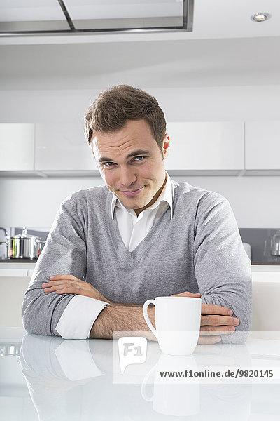 Porträt eines lächelnden Mannes in der Küche mit einer Tasse Kaffee