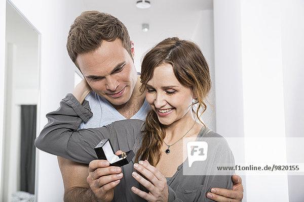 Mann präsentiert seiner Freundin einen Ring