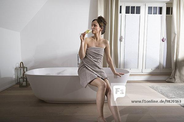 Woman sitting on the edge of modern bathtub drinking champagne
