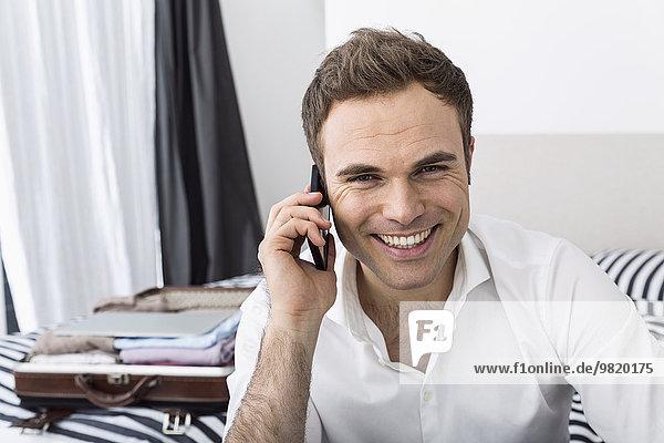 Lächelnder Geschäftsmann sitzt auf dem Bett und telefoniert mit dem Smartphone.