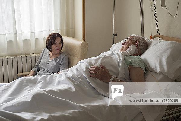 Frau  die sich um den älteren Mann kümmert  der sich nach der Operation erholt.