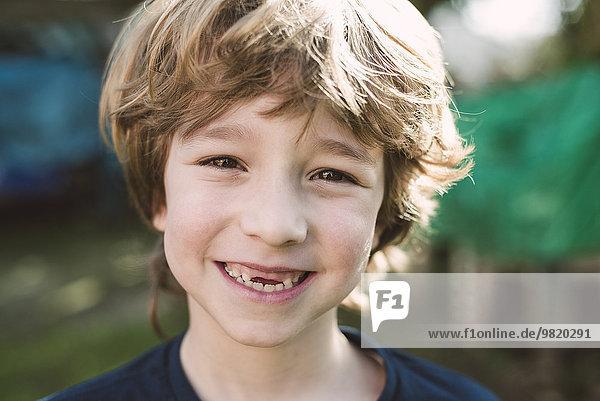 Porträt eines blonden Jungen mit einem großen Lächeln