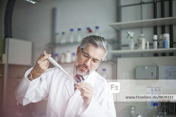 Wissenschaftler gießt Flüssigkeit in ein Reagenzglas