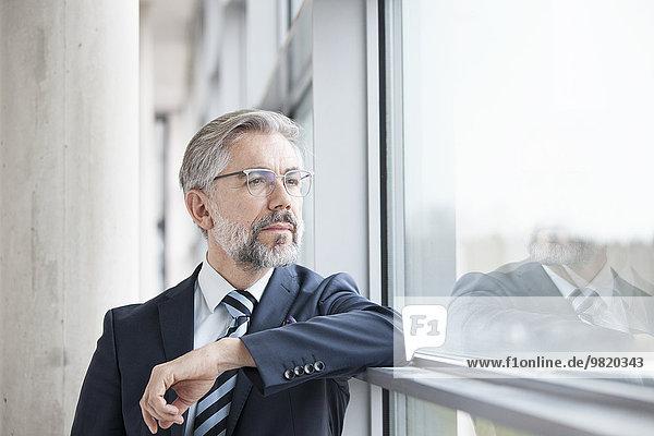 Nachdenklicher Geschäftsmann  der aus dem Fenster schaut.