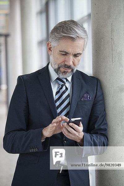 Geschäftsmann  der sich mit dem Smartphone gegen die Säule lehnt