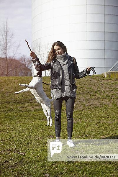 Deutschland  Düsseldorf  Junge Frau spielt mit ihrem Hund
