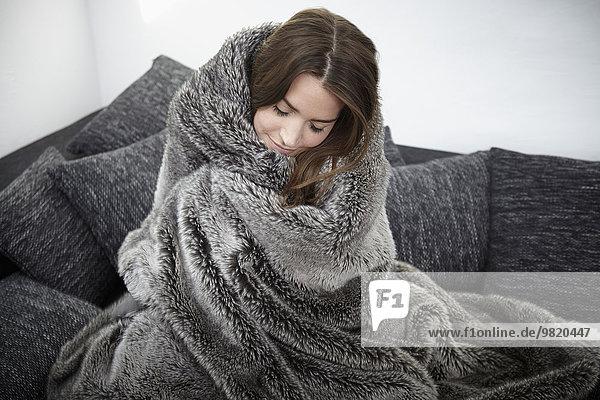 Junge Frau auf Couch in Pelzdecke gewickelt