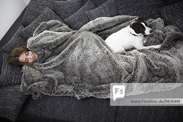 Young woman wrapped in fur blanket relaxing on couch with dog