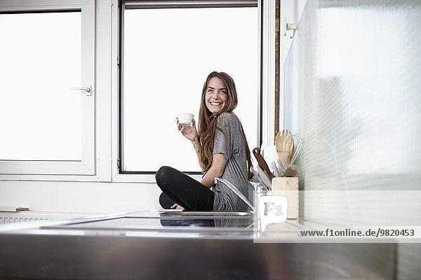 Junge Frau in der Küche sitzt am Fenster und trinkt Kaffee.