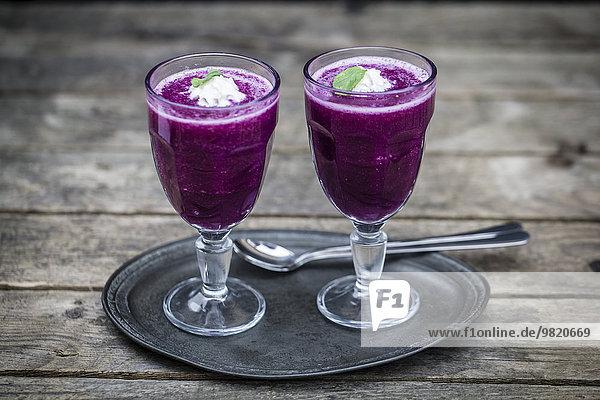 Zwei Gläser Rotkohl-Gazpacho auf Metallplatte