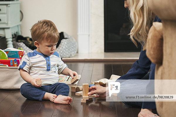Mutter und kleiner Sohn spielen mit Bausteinen