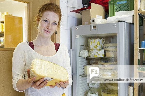 Porträt einer lächelnden jungen Frau im Vollwertladen mit einem Stück Käse