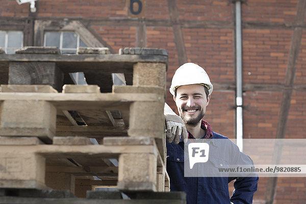 Lächelnder Arbeiter hinter Paletten