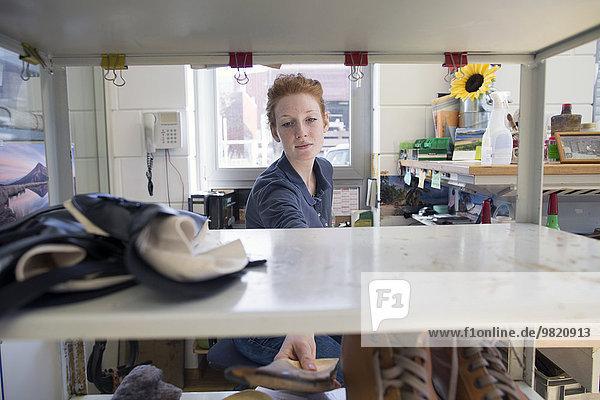 Schuhmacherin nimmt Einlegesohle aus dem Regal