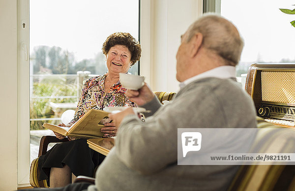 Senior couple with photo album drinking coffee at home