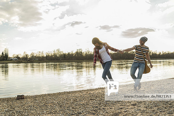 Happy young couple at the riverside walking hand in hand