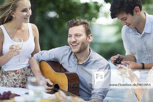 Glückliche Freunde mit Wein und Gitarre im Freien