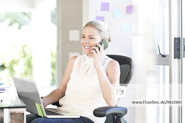 Geschäftsfrau mit Laptop-Telefonie im Büro